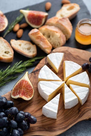 Camembert cheese plate with grapes, figs, honey and baguette. Cheese platter