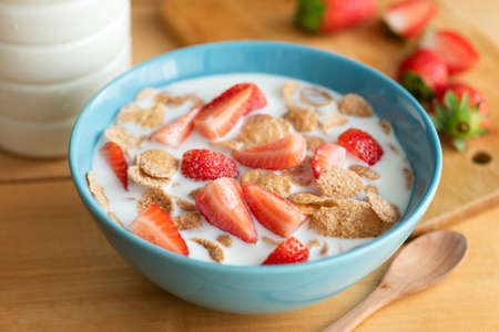 Whole grain flakes with milk and strawberries in a bowl on wooden table. Healthy nutritious breakfast food Stock Photo
