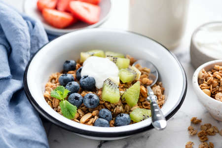 Granola bowl with blueberry, kiwi fruit and greek yogurt. Clean eating, sustainable food concept
