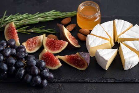 Camembert cheese with figs, grapes and honey. Cheese platter on black slate Stock Photo