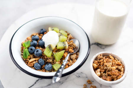 Granola with fruits and yogurt in bowl on marble table background. Sustainable food, clean eating concept