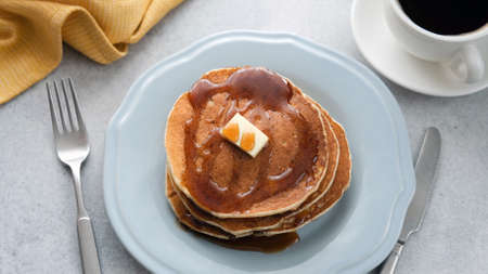Pancakes with butter and maple syrup on plate, breakfast food