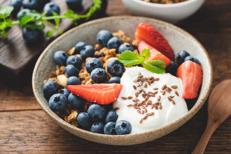 Healthy breakfast food with greek yogurt, crunchy oat granola and fruits on a wooden table. Sustainable eating