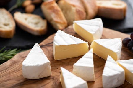 Sliced brie cheese or camembert on wooden board. Tasty french soft cheese