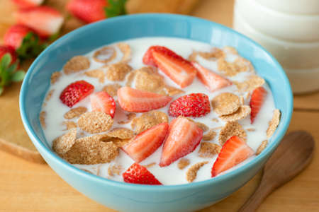 Whole grain flakes with wheat bran, strawberries and almond milk in a blue bowl for a healthy breakfast Stock Photo