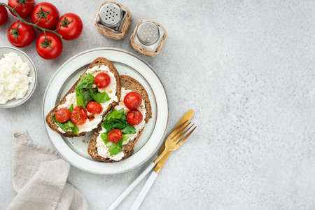 Healthy italian bruschetta with ricotta cheese, romaine lettuce and roasted cherry tomatoes. Table top view, copy space Stock Photo