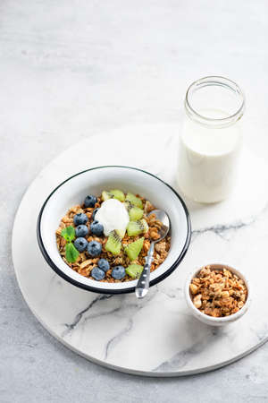 Bowl of granola with blueberries, kiwi and yogurt. Healthy breakfast food, clean eating concept