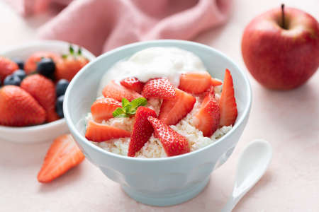 Tvorog, cottage cheese with strawberries in bowl. Healthy dairy food rich in Calcium, Protein. Diet food
