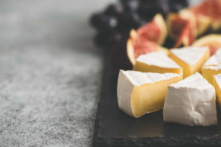 Sliced brie or camembert cheese with figs and grapes on black slate board. Cheese plate, copy space