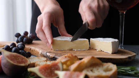Preparing cheese plate with soft camembert cheese, figs and grapes. Womans hands slicing cheese Stock Photo