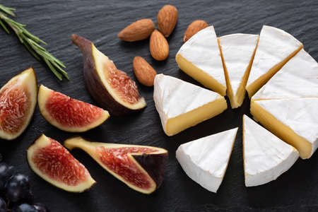 Camembert cheese with figs and almonds on black slate. Cheese appetizer plate