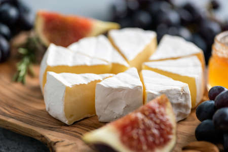 Camemebert cheese with figs, grapes and honey on wooden board, closeup view Stock Photo