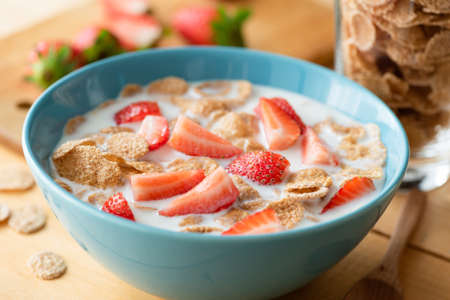 Whole grain flakes with milk and strawberries. Breakfast cereals with milk in blue bowl
