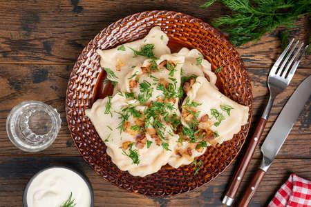 Pierogi with fried onions and chopped dill. Healthy steamed dumplings stuffed with potato. Polish, Ukrainian cuisine food. Varenniki