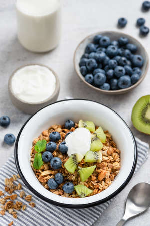 Breakfast granola bowl with fruits and yogurt. Clean eating, dieting, fitness lifestyle concept Stock Photo