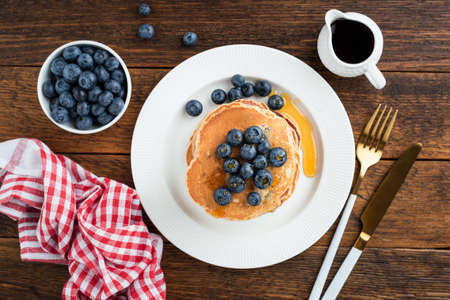 Pancakes with blueberries and maple syrup on a wooden table background, top view Stock Photo
