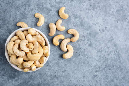 Cashews in bowl on concrete background, top view copy space