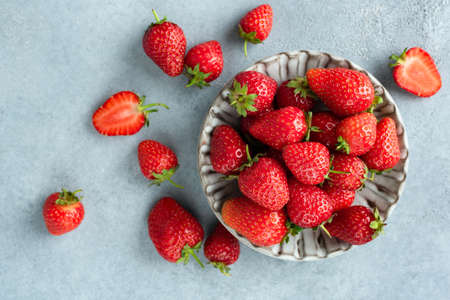 Strawberries on grey concrete background. Top view. Organic red berries