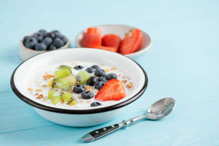 Breakfast bowl with almond milk, fruits and granola on a blue background with copy space for text or design. Closeup view