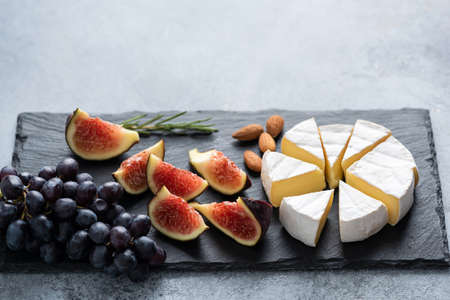 Brie cheese with figs and grapes on black slate. Gourmet cheese platter