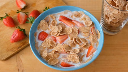 Whole grain flakes with milk and strawberries in blue bowl on wooden table. Healthy breakfast food Stock Photo