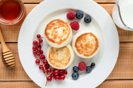 Curd cheese fritters, syrniki with fresh summer berries on a plate, wooden background. Top view. Sweet breakfast food
