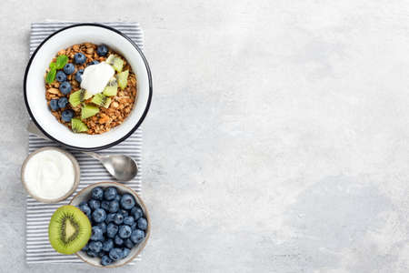 Granola bowl with fruits and yogurt on grey concrete background. Top view, copy space. Healthy eating, sustainable lifestyle concept