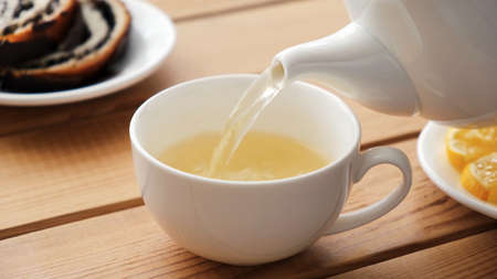 Pouring green tea in white porcelain cup. Closeup view