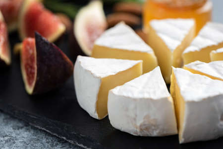Sliced camembert cheese and figs on black slate, closeup view. Gourmet cheese plate