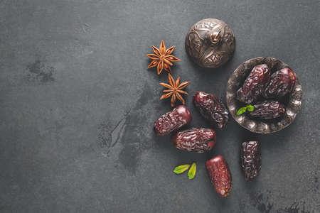 Dried dates, dried fruit on black background. Top view copy space. Arabic Islamic food Standard-Bild