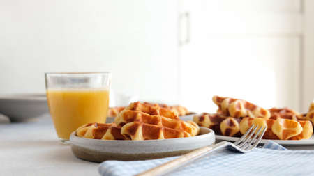 Belgian waffles and orange juice breakfast on a table