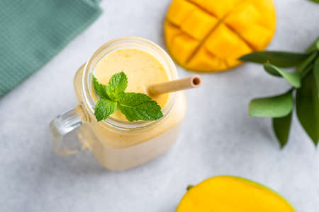Mango smoothie in glass jar with eco bamboo drinking straw decorated with mint leaf on grey concrete background Standard-Bild