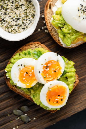 Toast with mashed avocado and egg garnished with sesame seeds. Healthy avocado open sandwich Standard-Bild
