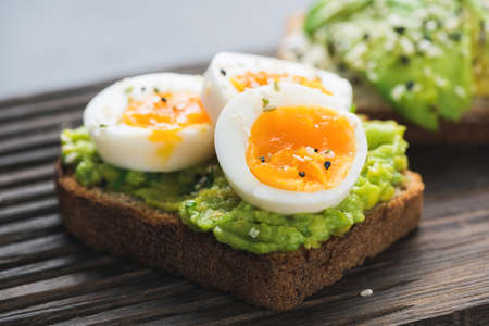 Avocado toast with egg on wooden board, closeup view Standard-Bild