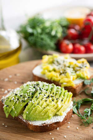 Toast with avocado, cream cheese and sesame seeds for healthy breakfast or snack