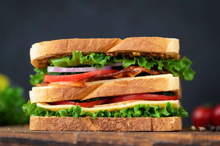 Club sandwich with bacon. Big tasty sandwich with lettuce, tomato, cheese, bacon and ham