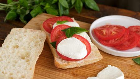 Caprese panini sandwich on wooden board. Italian food appetizer