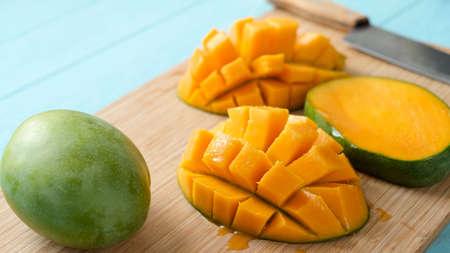 Delicious ripe mango cut in chunks on a wooden cutting board. Tropical fruit juicy mango