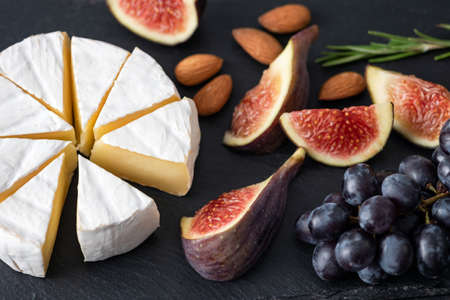 Camembert cheese with figs and grapes on black slate background. Appetizer cheese platter