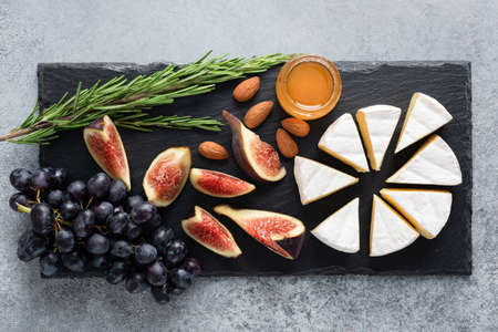 Camembert cheese platter with figs, grapes, honey and nuts served on black slate. Top view