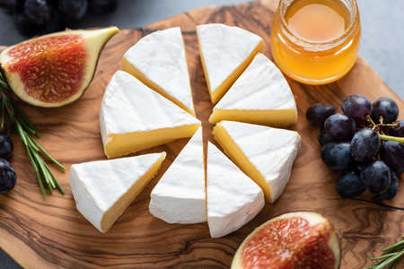 Camembert or brie cheese with figs, grapes and honey on wooden serving board. Cheese plate Standard-Bild