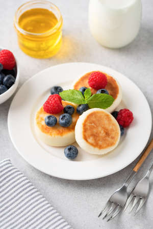 Cottage cheese fritters Syrniki served with summer berries and honey. Russian, Ukrainian cuisine food