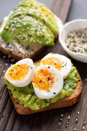 Whole grain toast with avocado and egg on wooden table. Healthy breakfast lunch or snack avocado bruschetta
