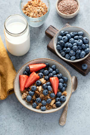 Berry and granola bowl with bottle of almond milk, healthy breakfast food