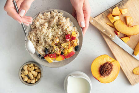 Oatmeal bowl with peach and hemp seeds in female hands. Clean eating, dieting, vegan food concept