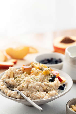 Healthy oatmeal porridge with fruits and hemp seeds for breakfast. Vegan, vegetarian breakfast food concept