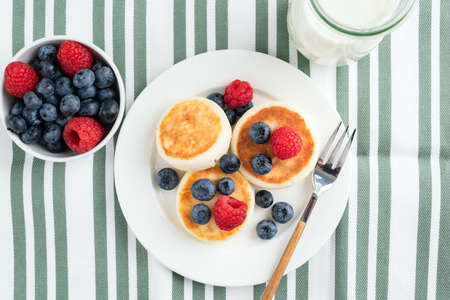 Cottage cheese fritters with summer berries blueberries and raspberries. Syrniki, cheese pancakes