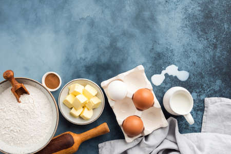 Ingredients for baking on blue background. Flour eggs butter spices and milk