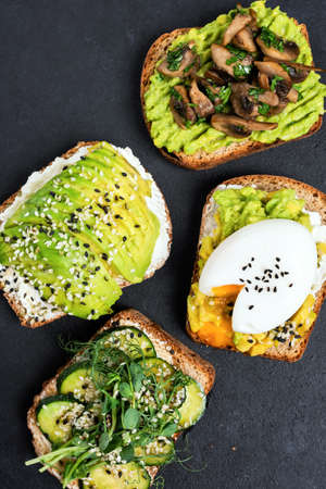Assortment of avocado toasts. Healthy toast with avocado, egg, fried mushrooms, cucumber and microgreens garnished with sesame seeds. Top view on black concrete background