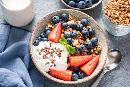 Granola bowl with yogurt and berries in a bowl. Healthy breakfast food Standard-Bild